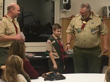 Troop Leader Speaks Next to Boy Scout